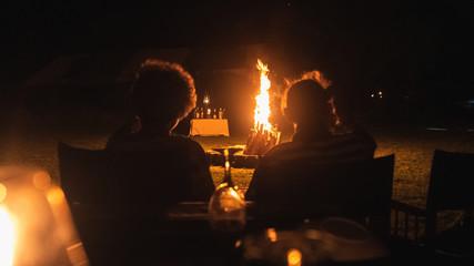 Senior couple traveller sitting in front of a bonfire in camp in Sri Lanka