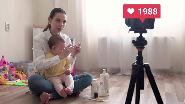 Young pretty mother with baby recording vlog or doing live stream and going virel with liked counter 4k