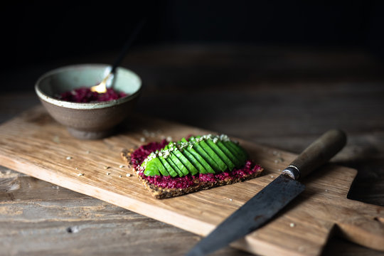 Seed cracker with avocado slices, beet hummus and hemp seeds on a rustic wooden board and a rustic table served with  beet hummus in a pottery bowl with a rustic knife. Close up side view copy space.