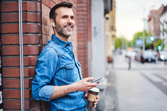 Man chatting on phone through wireless headphones and having coffee