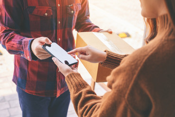 woman receiving parcel box and signing name on the phone from delivery man at the house's door