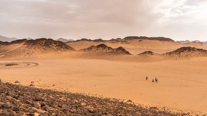 Travellers walking in a sacred valley in Sahara Desert, Algeria
