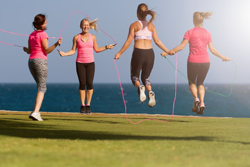 Group of young people doing their fitness training by the sea, using skipping rope