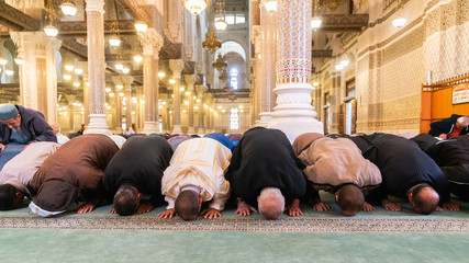 Muslim men bowing, kneeling and praying inside of a big mosque in Constantine, Algeria