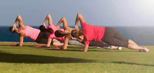 Four fit young women doing pilate exercises against fitness interface, on grass near sea