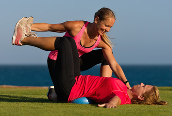 Fitness trainer helps the girl to do the exercises on green grass by the sea