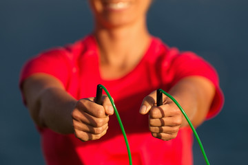 Sports woman holds a skipping rope in his hands is engaged in gymnastics against the background of the sea coast