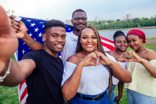 Group of girls and boys smiling with American flag in spring park autumn evening learning English language exchange students