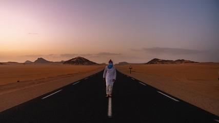 Man walking in a desert road in Sahara Desert during sunset