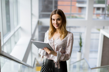 Attractive businesswoman using a digital tablet while standing on the stairs in the office