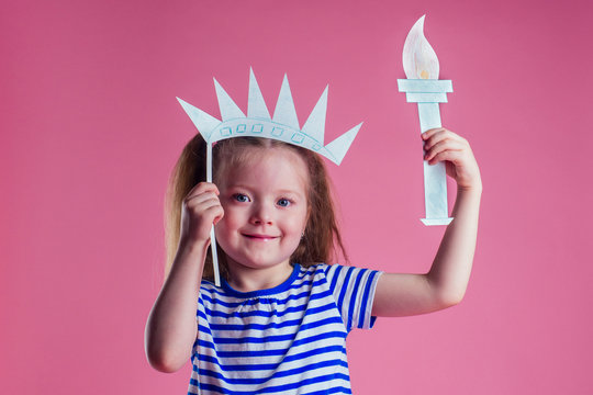 redhead blonde charming female kid celebration independence holding a paper torch and diy crown on a pink background in the studio.English language learning concept and freedom