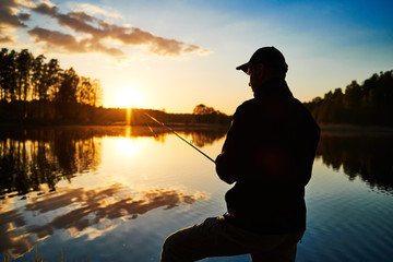 sunset fishing. fisher with spinning rod
