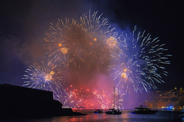 View from water surface on an amazing show of fireworks against the background of historical bastions of Valletta in Grand Harbor, Malta