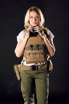Gorgeous young woman with long blonde hair wearing Military gear, posing isolated in studio over dark background