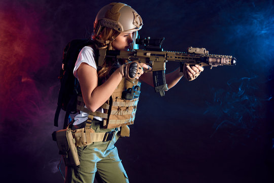 Heavily armed and well-equipped female soldier in battle helmet holding assault rifle isolated on dark smoky battlefield. Paint ball and laser tag sport games