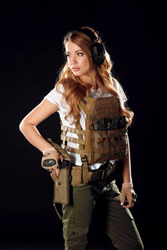 Calm and concentrated woman soldier possessing such features as battle and stress resistance and good coordination of movements holds gun in hands. Army, dedication, weapon, technology.