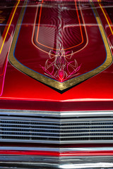 Detail of the hood of a red and chrome car with hand-painted lines