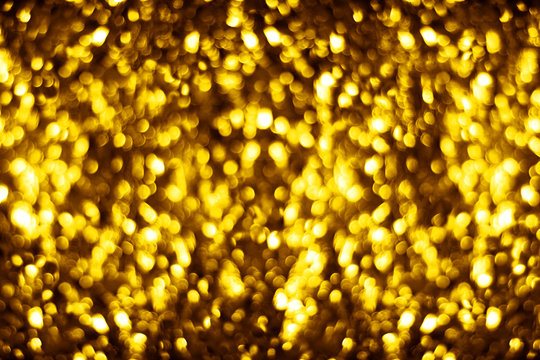 Blurred golden shiny glitter bokeh background, defocused yellow shimmer backdrop design, gold shining round bubbles blur effect, festive New Year and Christmas holiday banner concept, copy space
