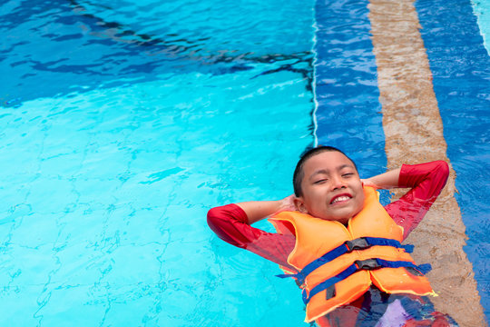 Asian boy smiling in his holiday and wear life jacket near the swimming pool.