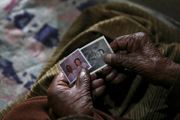 Shyam Saran Negi, 102, independent India's first voter who has participated in all elections since 1951, shows his old photos as he sits inside his house ahead of final phase of general election, in Kalpa