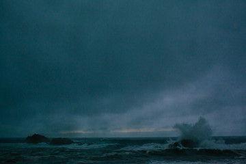 Waves of a raging dark sea crashing on rocks