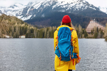 Outdoor shot of female hiker stands back at camera with big blue rucksack, wears yellow raincoat and red headgear, poses at coast of mountain lake, admires majectic nature scenery. Snow mountains Wall mural
