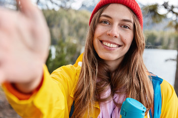 Optimistic female model has toothy smile, stretches hand as makes selfie, dressed casually, enjoys vacation in mountains, poses at beautiful place near lake, drinks hot tea from flask. Tourism concept