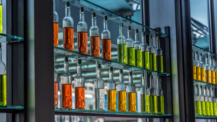 Flaschen mit bunter Flüssigkeit in einem Regal mit Glasböden