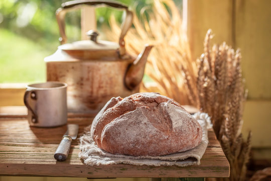 Fresh and big loaf of bread in spring sunny kitchen