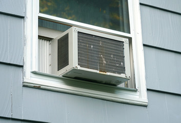 old air conditioner installed on rustic house window