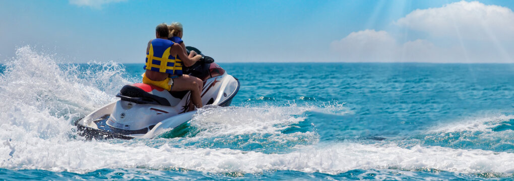 Happy crazy friends diving from Water bike into the sea - Young people jumping inside ocean in summer vacation - Travel and fun concept. Space for text. Panoramic view