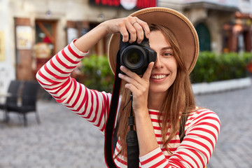 Professional photographer makes amateur photos while strolls in city during excursion, smiles positively, wears headgear, casual jumper, poses in urban setting. People, hobby, recreation concept