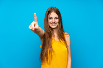 Young woman with long hair over isolated blue wall showing and lifting a finger Fototapete