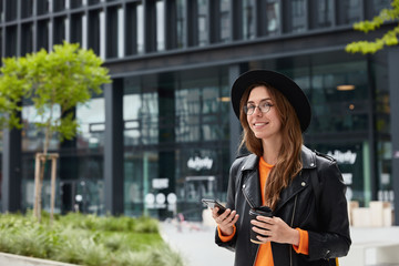 Young female blogger in stylish outfit uses modern cell phone and free internet connection for searching website, holds disposable cup of drink, strolls outdoors in city. Lifestyle and leisure concept