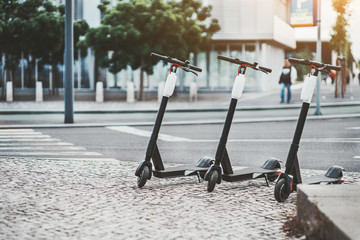 Electric urban transportation: three modern electric readies to ride scooter bikes with accumulators in the center of a city on the pavement stone with the road and crosswalk behind, Lisbon, Portugal