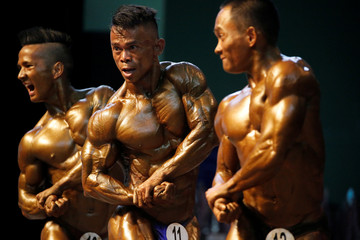 Bodybuilders flex their muscles on stage during the 16th Southeast Asia Bodybuilding and Physique Sports Championships in Yangon