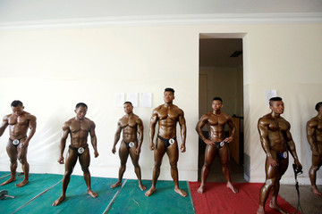 Bodybuilders wait backstage during the 16th Southeast Asia Bodybuilding and Physique Sports Championships in Yangon