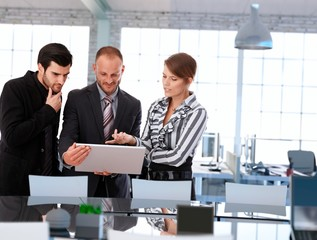 Businesspeople looking at laptop in modern office