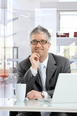 Happy mature businessman thinking at office desk