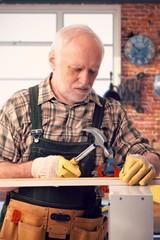 Senior handyman hammering at DIY home workshop