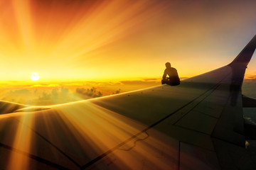 Adventure Travel Conceptual Photo of Silhouette of Man Sitting on Airplane Wing Watching Stunning Sunset World Destination