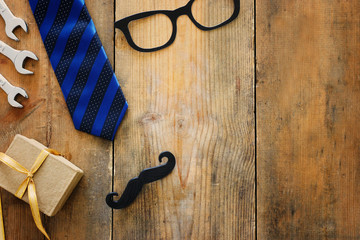 Father's day concept. gift box, tie and funny moustache over wooden background. top view, flat lay
