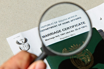 A hand holding an official South African marriage certificate. Getting married in court (home affairs) concept image.
