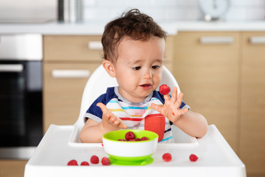 Baby in high chair with raspberry on finger