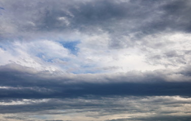 Dramatic dark clouds on blue sky background and texture