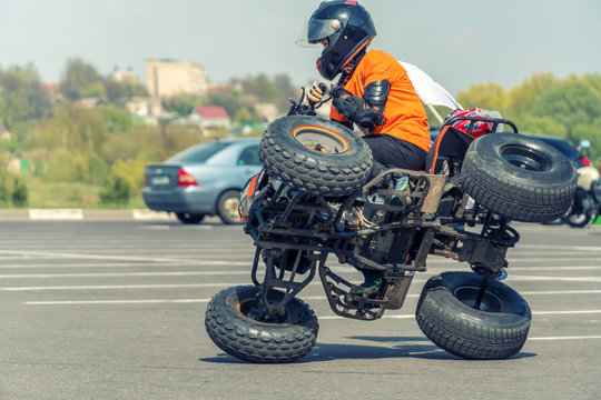 Extreme acrobatics on a Quad bike. A teenage child performs tricks on a Quad bike. The Quad bike is on two wheels sideways.