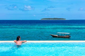 Foto auf Gartenposter Sansibar one caucasian woman enjoying vacations sunbathing on a infinity swimming pool by the seaside looking at the idian ocean Muyuni in Unguja aka Zanzibar Island Tanzania East Africa