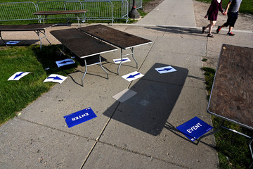 "Placards of arrows and others stating ""ENTER"" and ""EVENT"" lay scattered on the ground, as a couple walks holding hands, after the kickoff rally for Democratic 2020 U.S. presidential candidate and former Vice President Joe Biden in Philadelphia"