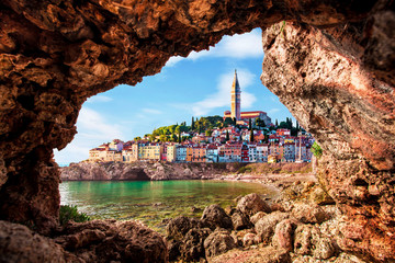 Unusual view with old clock towe in Piran through a rock hole. the tourist center of Slovenia....