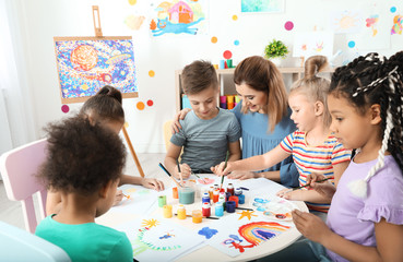 Children with female teacher at painting lesson indoors